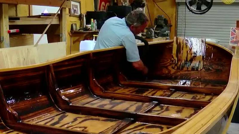 A son is carrying on his father's boat-making business.