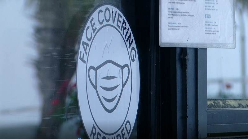 A sign at an Ocean Boulevard business shows face coverings are still required upon entry.