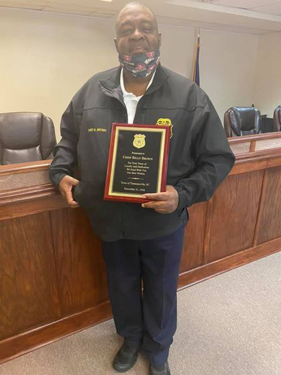 Outgoing Timmonsville Police Chief Billy Brown stands with plaque commemorating his dedication...