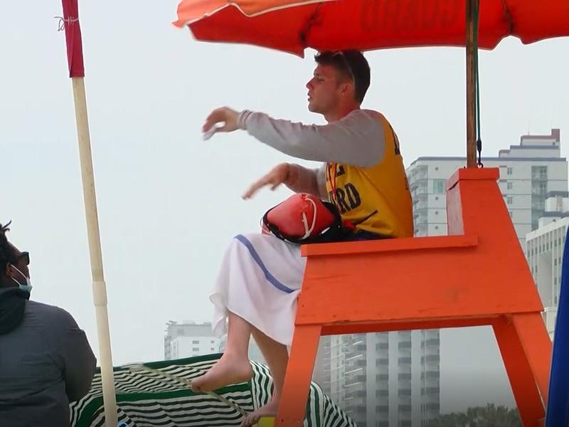 Lack's Beach Services Lifeguard Julen Alonso talks with a beach attendant.
