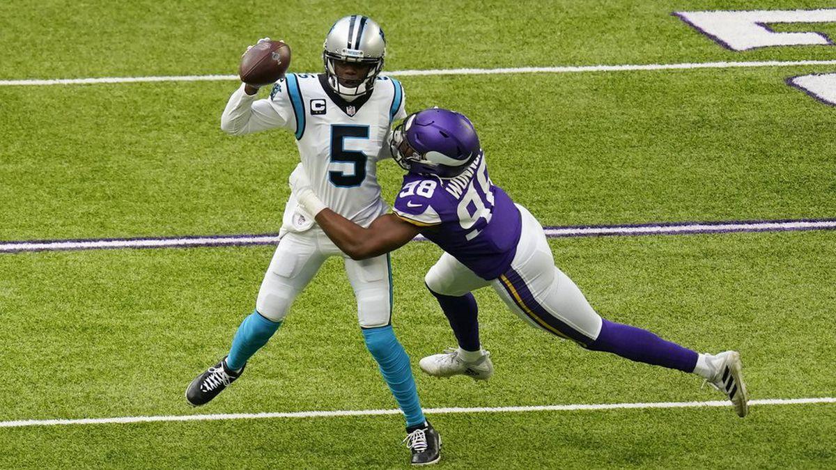 Carolina Panthers quarterback Teddy Bridgewater (5) tries to break a tackle by Minnesota...