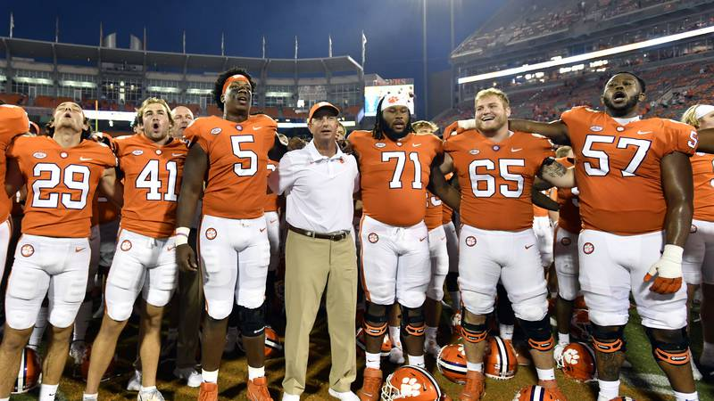Clemson head coach Dabo Swinney, center, joins his team in singing the Clemson alma mater after...