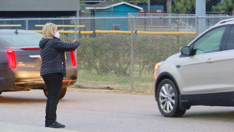 An employee directs traffic and prepares to hand out vouchers for the COVID-19 vaccine. No...