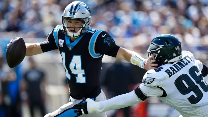 Carolina Panthers quarterback Sam Darnold pushes off Philadelphia Eagles defensive end Derek...