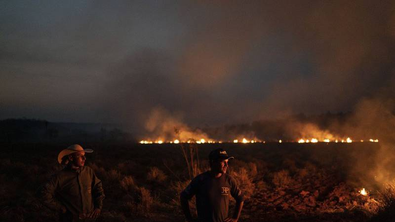 Neri dos Santos Silva, center, watches an encroaching fire threat after digging trenches to...