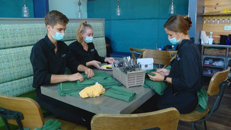 Servers at Hook and Barrel in Myrtle Beach roll silverware ahead of their shift. The restaurant...