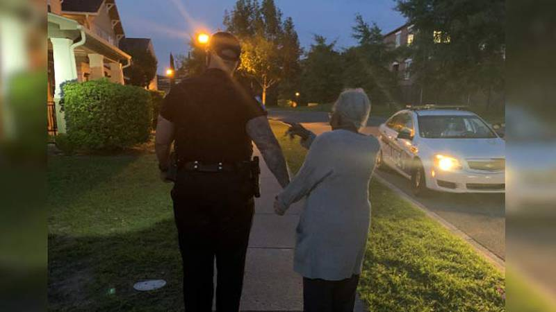 North Charleston Police shared a photo of one of its officers walking with a woman family...