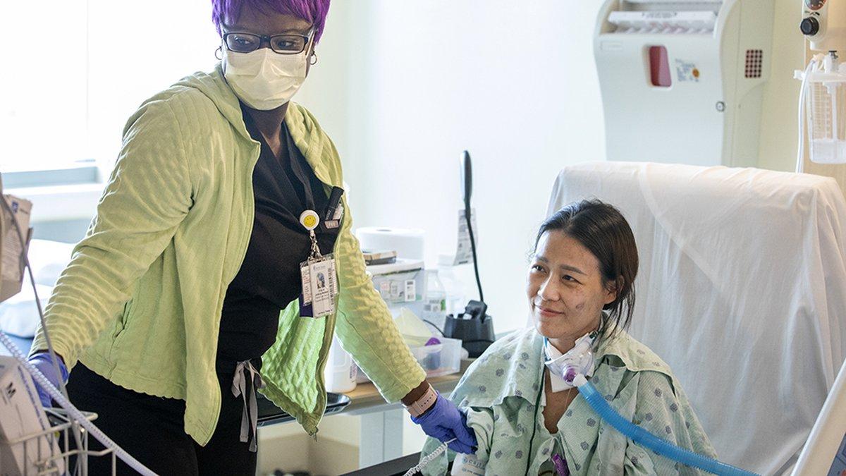 Patient care tech Octavia Jenkins-Watson checks Prem Koonkhuntod's vital signs. Koonkhuntod is...
