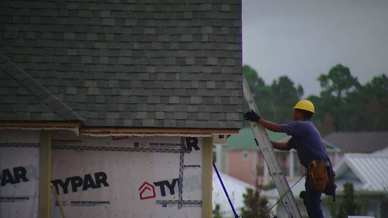 A construction worker helps build a house in Horry County.