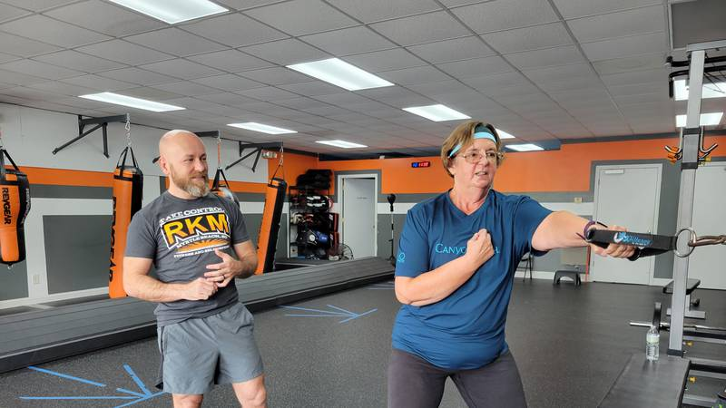 RKM Owner Mike Pesesko helps a member with her workout