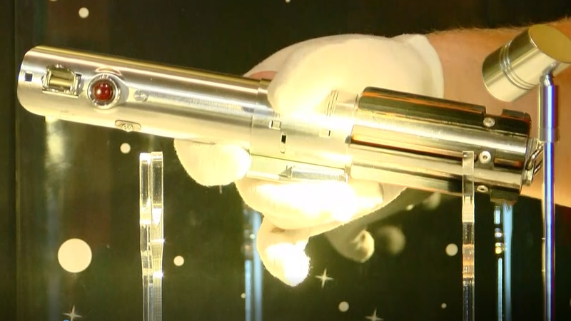 A manager places Luke Skywalker's iconic lightsabre in a display case at Ripley's Believe It or...