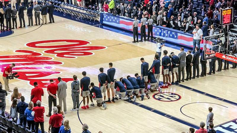Six Mississippi basketball players take a knee during the national anthem before an NCAA...