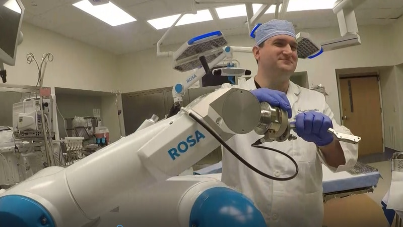 Dr. Christopher Walsh puts an attachment on Rosa the Robot.