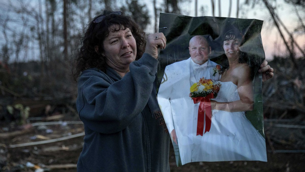 Carol Dean holds up her wedding photo to show family members after finding it in the rubble of...