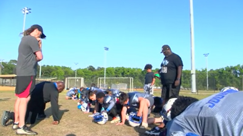 Kneeling with head down in prayer, coach Evins Nicholson recites the Lord's prayer to his...