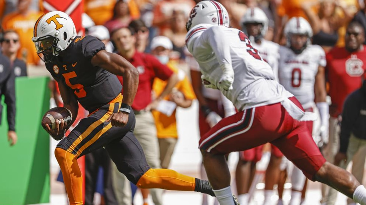 Tennessee quarterback Hendon Hooker (5) runs for yardage as he's chased by South Carolina...