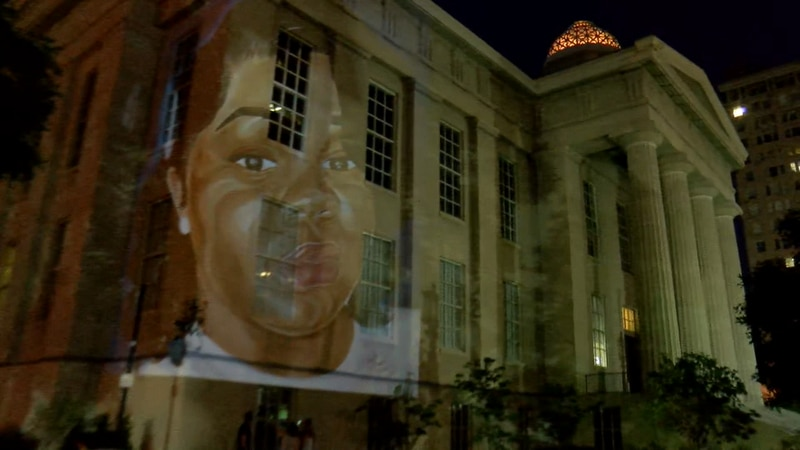 A Louisville artist unveiled a painting in dedication to Breonna Taylor by projecting the work...