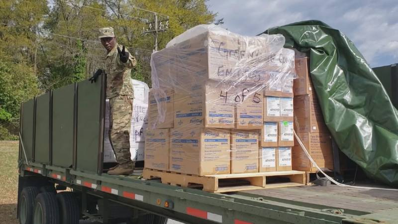 A member of South Carolina's National Guard assists health officials in distributing medical...