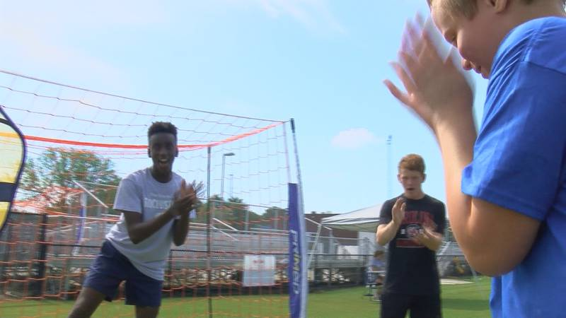 Lashaun Scott and classmates cheer on a Special Olympian to score a goal.