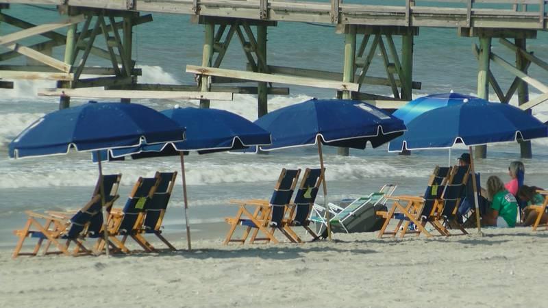 Beachgoers sit along the coast near the Cherry Grove Pier.