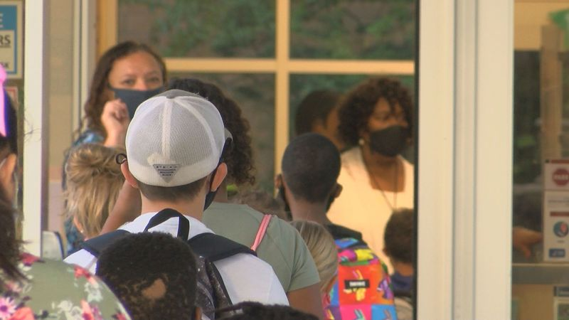 Students with face masks line up 6 feet apart at the front of Conway Elementary School....