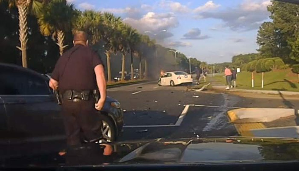 Pfc. Adrian Besancon, seen here in dashcam footage, runs toward a burning vehicle following the...